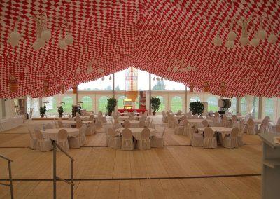 21 m Zeltbreite mit beidseitigen Anbauen je 4 m, Gesamtbreite 29 m, mit hängenden Dekorationsbahnen Raute rot/weiß