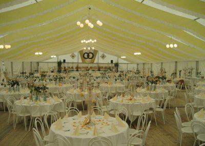 Hochzeitszelt, 21 m Zeltbreite mit händenden Dekorationsbahnen gelb-weiß und runder Bestuhlung