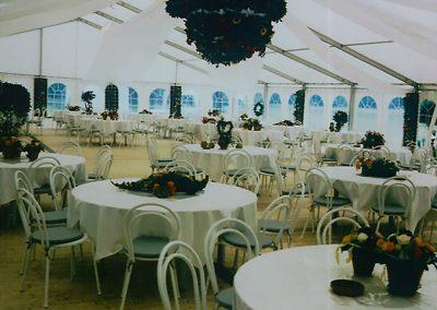 Hochzeitszelt mit Fenstervorhängen und runder Bestuhlung